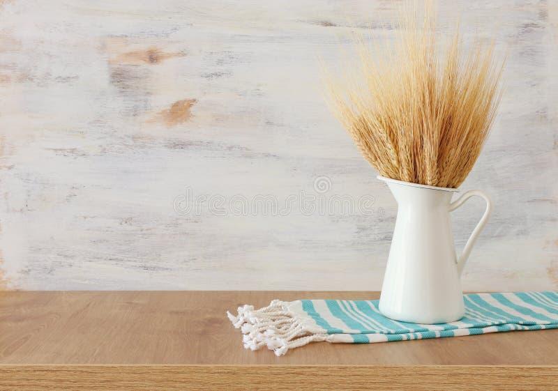 Cultures de blé et serviette de cuisine rurale au-dessus de table en bois et de fond blanc Symboles des vacances juives - Shavuot photo stock