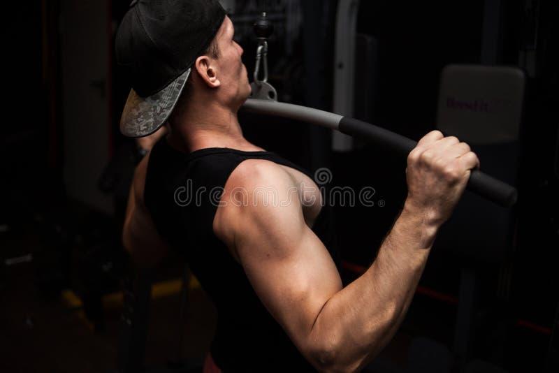 Culturista atlético muy potente del individuo, ejercicio para la parte posterior y manos un hombre en el gimnasio fotos de archivo