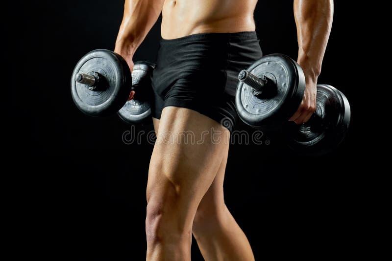 Culturista con pesas de gimnasia en negro imagenes de archivo