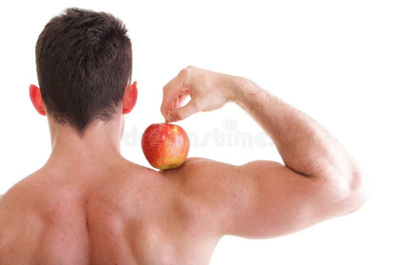 Culturista de sexo masculino atractivo atlético que sostiene la manzana roja fotografía de archivo