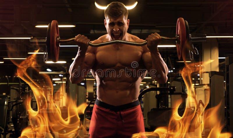 Culturista del hombre como un diablo en fuego imagenes de archivo