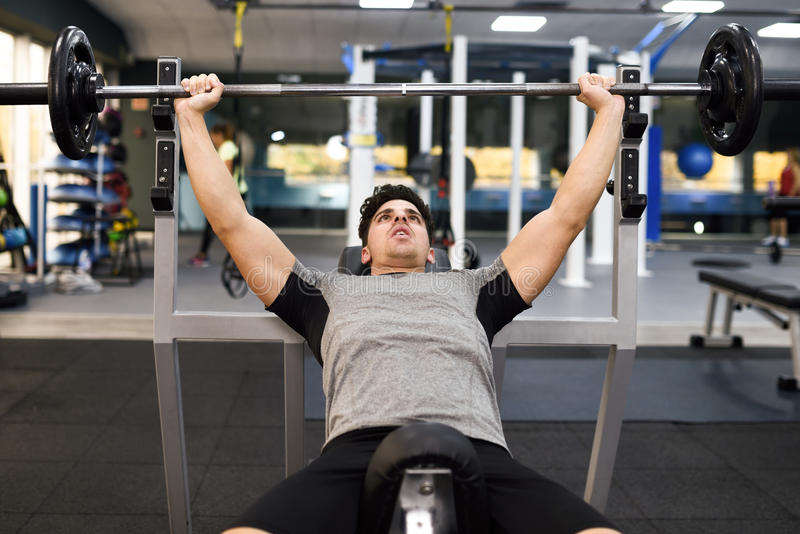 Culturista del hombre joven que hace el levantamiento de pesas en gimnasio imágenes de archivo libres de regalías