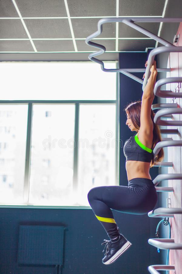 Culturista della donna di forma fisica che tira su alla palestra Foto di vista laterale fotografie stock libere da diritti