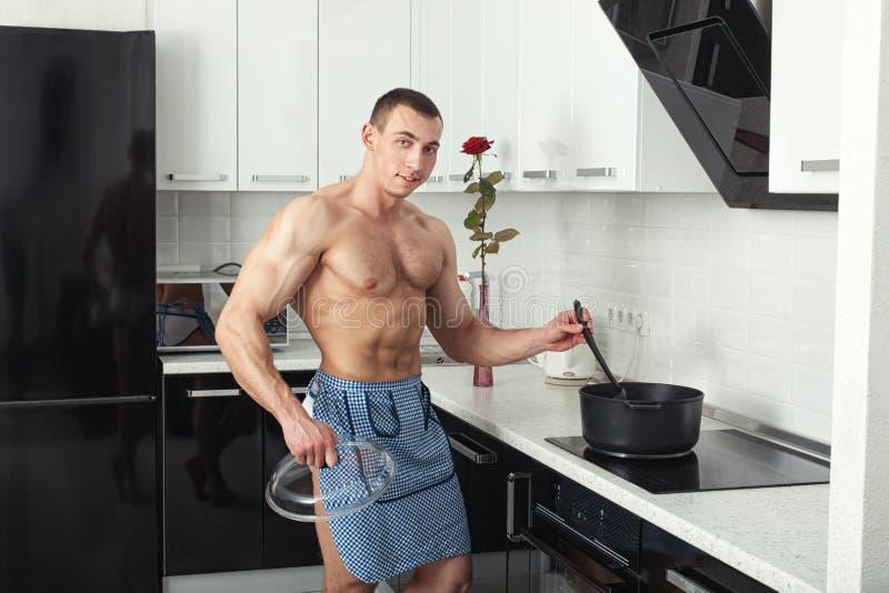 Culturista en la cocina cerca de la estufa imagen de archivo libre de regalías