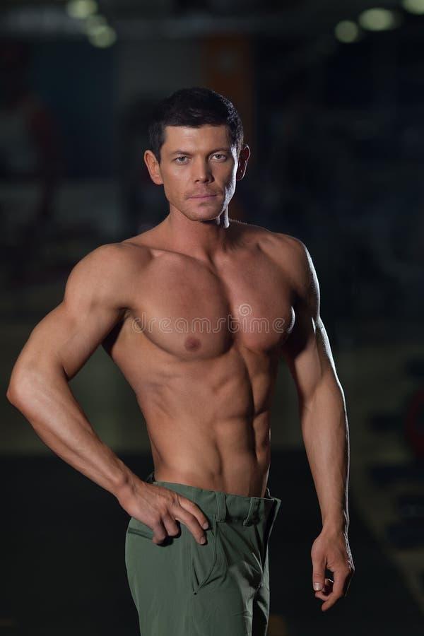 Culturista fuerte con el cuerpo bronceado muscular foto de archivo