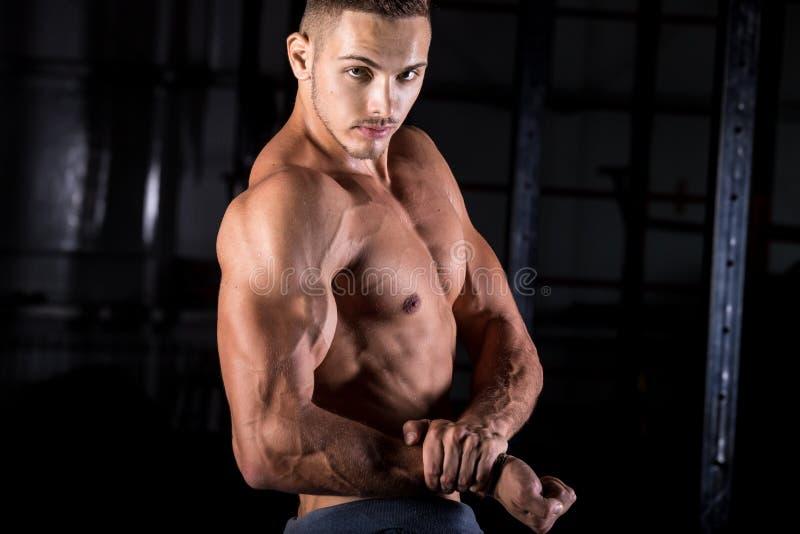 Culturista joven que muestra el bíceps fuerte imagen de archivo libre de regalías