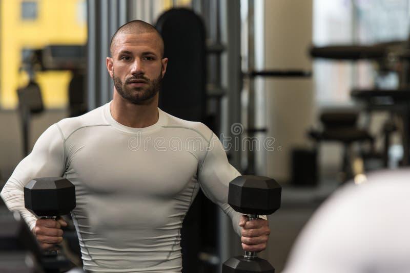 Culturista masculino joven que descansa entre los entrenamientos en gimnasio fotografía de archivo