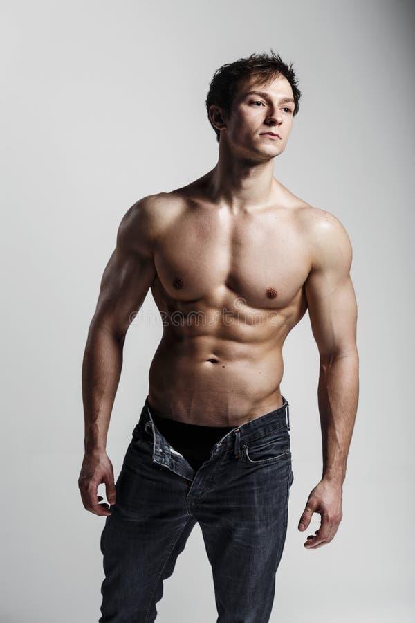 Culturista modelo masculino muscular con vaqueros desabrochados Estudio sh imagenes de archivo