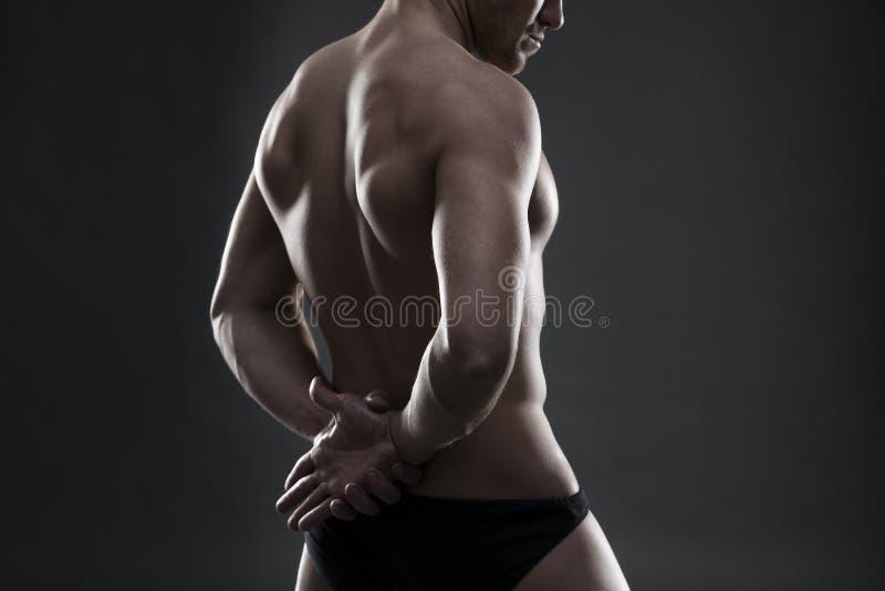 Culturista muscolare bello che posa sul fondo grigio Colpo scuro dello studio fotografia stock libera da diritti