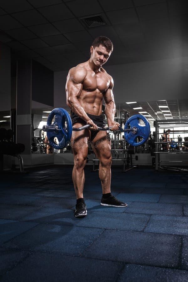 Culturista muscolare dell'atleta nell'addestramento della palestra con la barra immagini stock libere da diritti