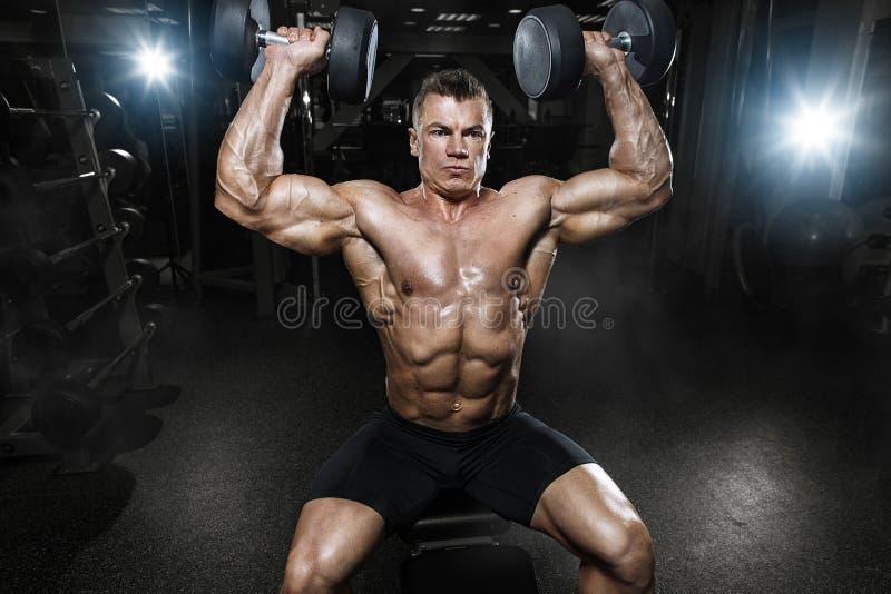 Culturista muscolare dell'atleta nell'addestramento della palestra con le teste di legno fotografia stock
