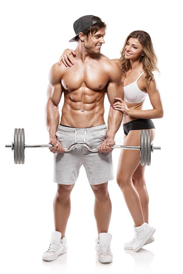 Culturista muscular con la mujer que hace ejercicios con pesas de gimnasia imagen de archivo