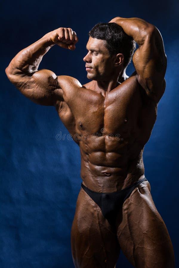 Culturista muscular hermoso que presenta sobre fondo azul fotografía de archivo libre de regalías