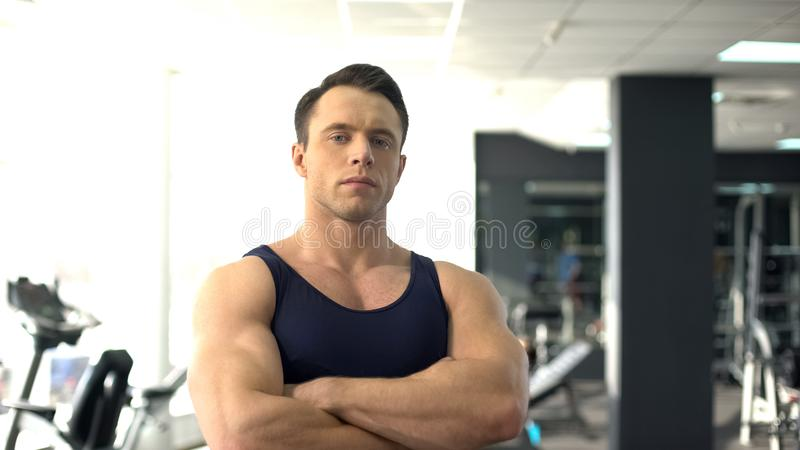 Culturista muscular que presenta, servicio del gimnasio, instructor personal, motivación del deporte imágenes de archivo libres de regalías
