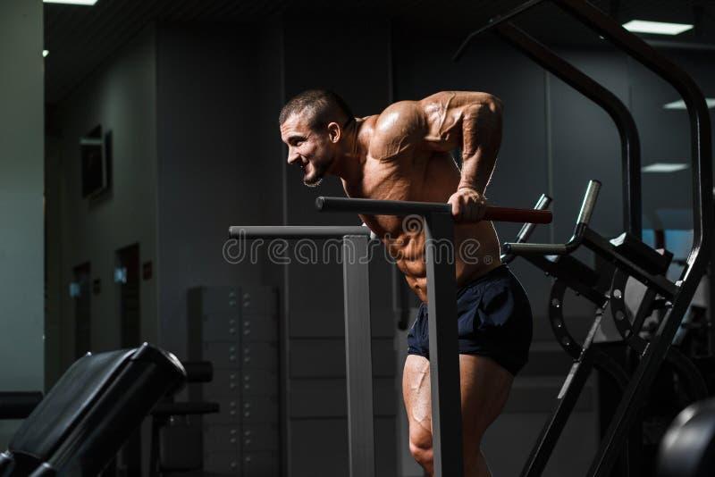 Culturista muscular que se resuelve en el gimnasio que hace ejercicios en paral foto de archivo libre de regalías