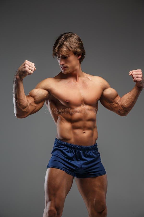 Culturista senza camicia impressionante negli shorts blu fotografia stock