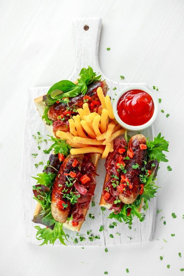 Cumberland kiełbasiani hot dog z karmelizującą cebulą, piec czerwoni pieprze, francuz smażą fotografia stock