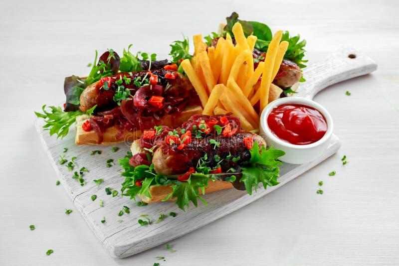 Cumberland-Wursthotdoge mit karamellisierter Zwiebel, gebratene rote Pfeffer, Pommes-Frites stockfoto