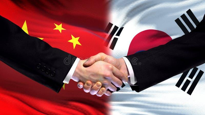 Cumbre internacional de la amistad del apretón de manos de China y de la Corea del Sur, fondo de la bandera imagenes de archivo