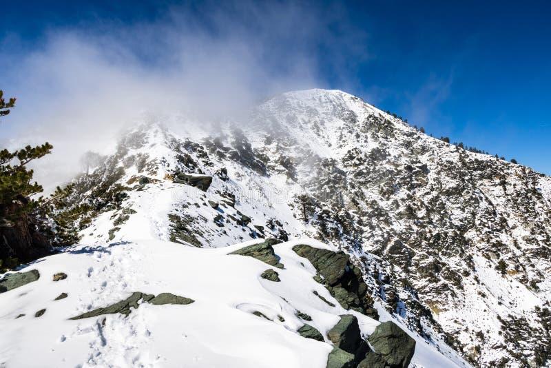 Cume rochoso na fuga para a parte superior da montagem San Antonio (Mt Baldy) em um dia nevado mas ensolarado, com a névoa que au imagens de stock