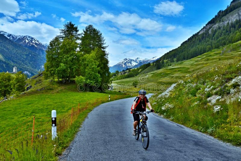 Cume-vista suíça no ciclista na estrada da montanha acima de Ardez fotografia de stock