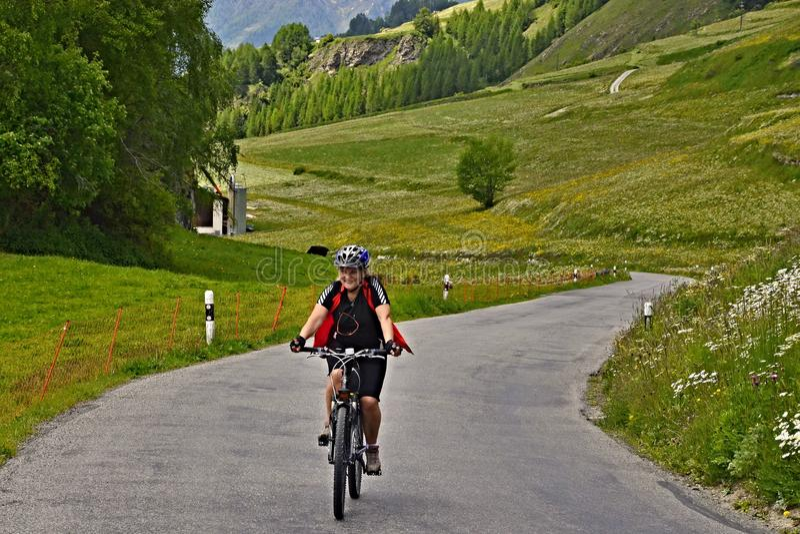 Cume-vista suíça no ciclista na estrada da montanha acima de Ardez imagem de stock royalty free