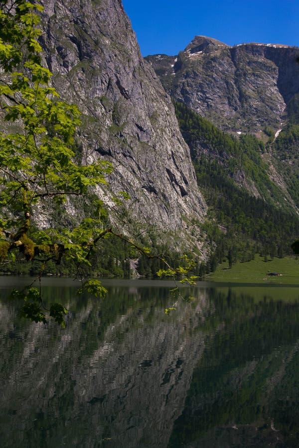 Cumes alpinos do lago na primavera Vista da costa da cabana do lago alpino Reflexão das montanhas no claro imagens de stock royalty free