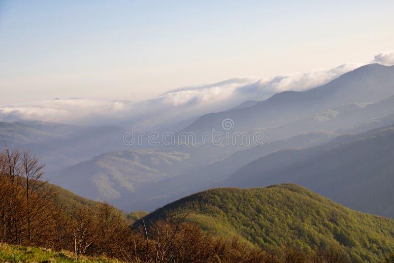 Cumes dos montes nas nuvens no por do sol imagem de stock royalty free
