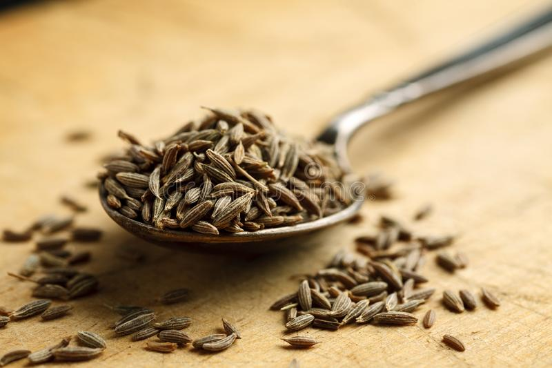 Cumin seeds in metal spoon on a wooden table, closeup. Dry, black, cuisine, culinary, flavor, food, ingredient, macro, spice, aromatic, background, cook royalty free stock photo