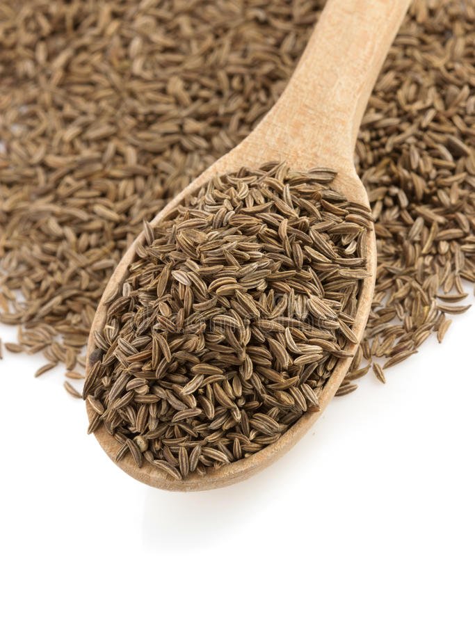 Cumin seeds in spoon. On white background royalty free stock photo