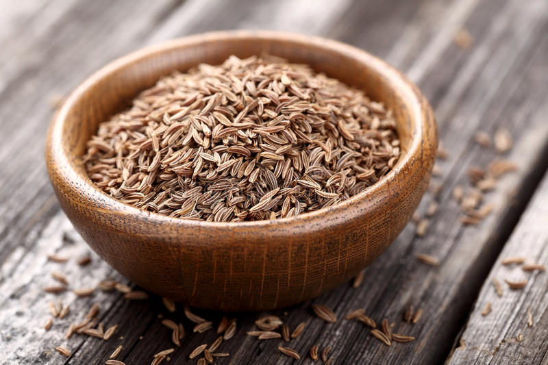 Cumin in a wooden plate stock photos