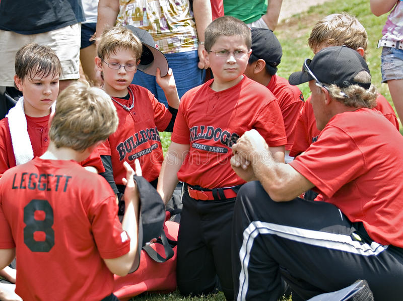CUMMING, GA,USA - MAY 15: A coach giving a pep talk to his base. A coach talking to his little league baseball team, families are in the background listening stock image