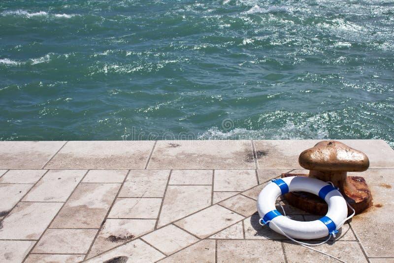 Cumownica i lifebuoy, lifebelt na molu morzem obrazy stock