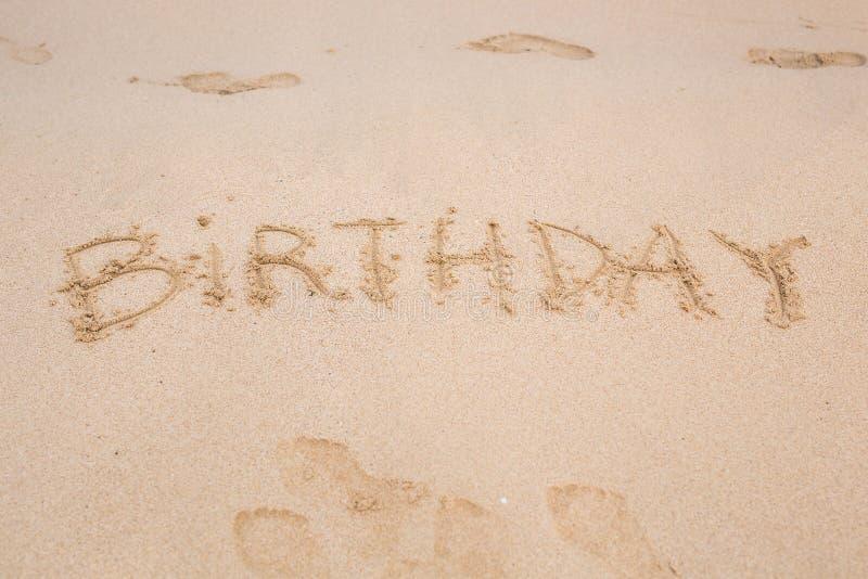 Cumpleaños escrito en la playa de la arena foto de archivo libre de regalías