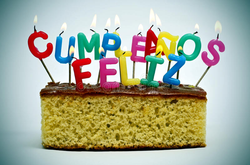 Cumpleanos feliz, happy birthday in spanish. Letter-shaped candles of different colors forming sentence cumpleanos feliz, happy birthday in spanish, on a cake royalty free stock image