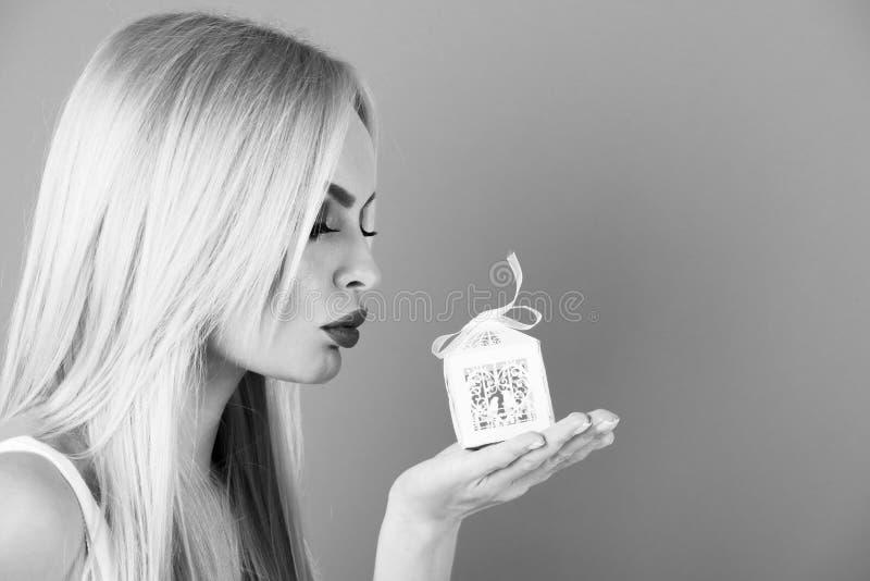Cumplido del regalo caja de regalo blanca de la muchacha o del control rubio atractivo de la mujer pequeña foto de archivo libre de regalías