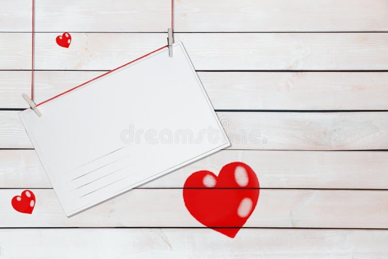 Cumprimentando o cartão de papel e três corações vermelhos no fundo branco de madeira com espaço da cópia imagem de stock