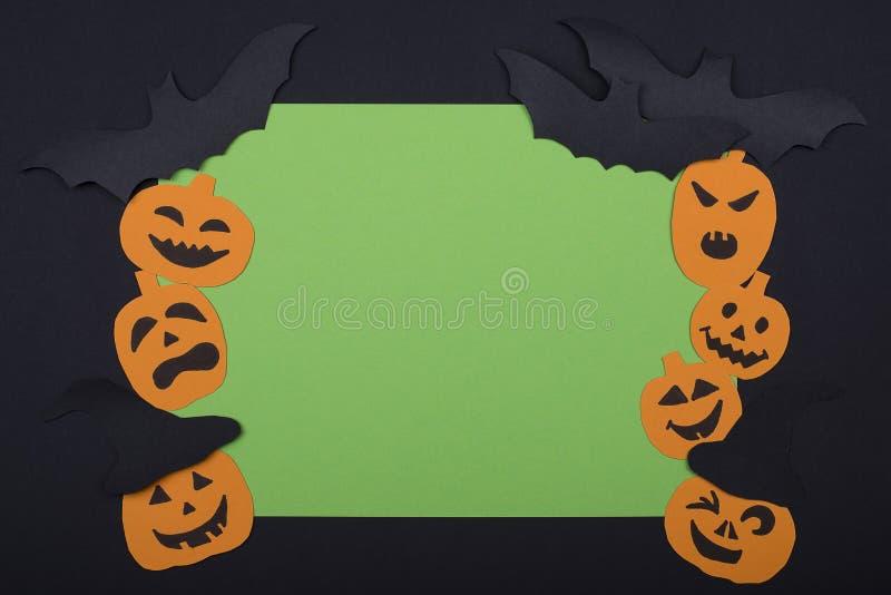 Cumprimentando o cartão verde feito a mão para Dia das Bruxas com as abóboras assustadores de sorriso, enegreça bastões em um fun fotos de stock