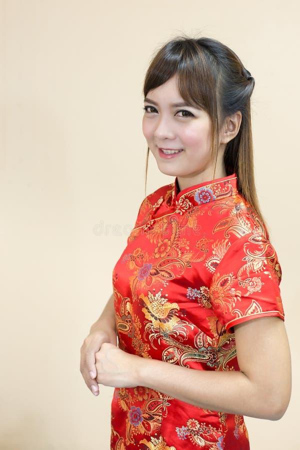 Cumprimento da mulher no chinês tradicional ou no cheongsam com expressão da boa vinda do elevador da mão e afortunado asiáticos  imagem de stock