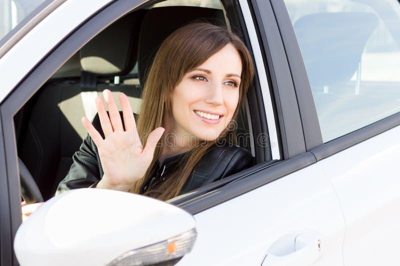 Cumprimento de sorriso novo da mulher com mão do carro imagens de stock