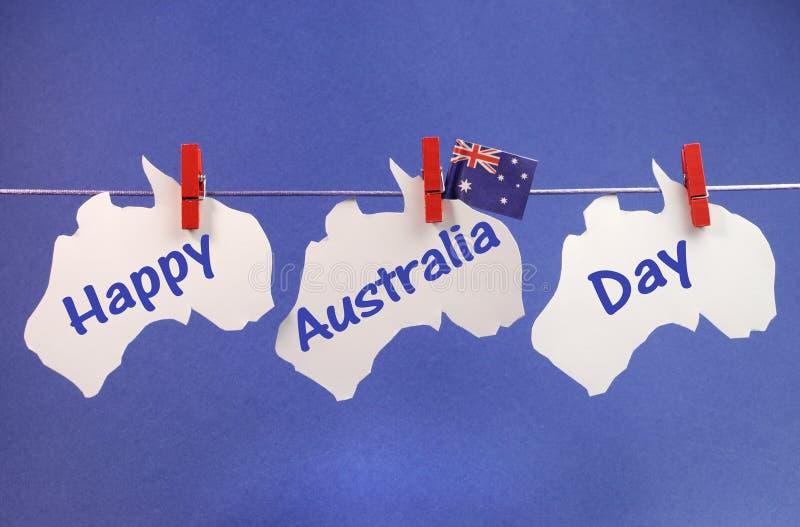 Cumprimento feliz da mensagem do dia de Austrália escrito através dos mapas australianos brancos e dos Pegs de suspensão da bandei imagem de stock royalty free