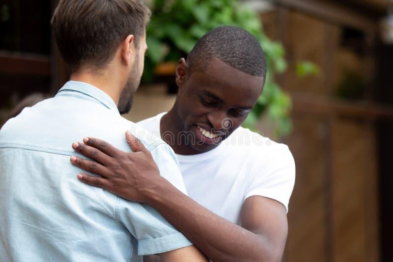 Cumprimento masculino multirracial feliz de dois melhores amigos que abraça no encontro fotos de stock