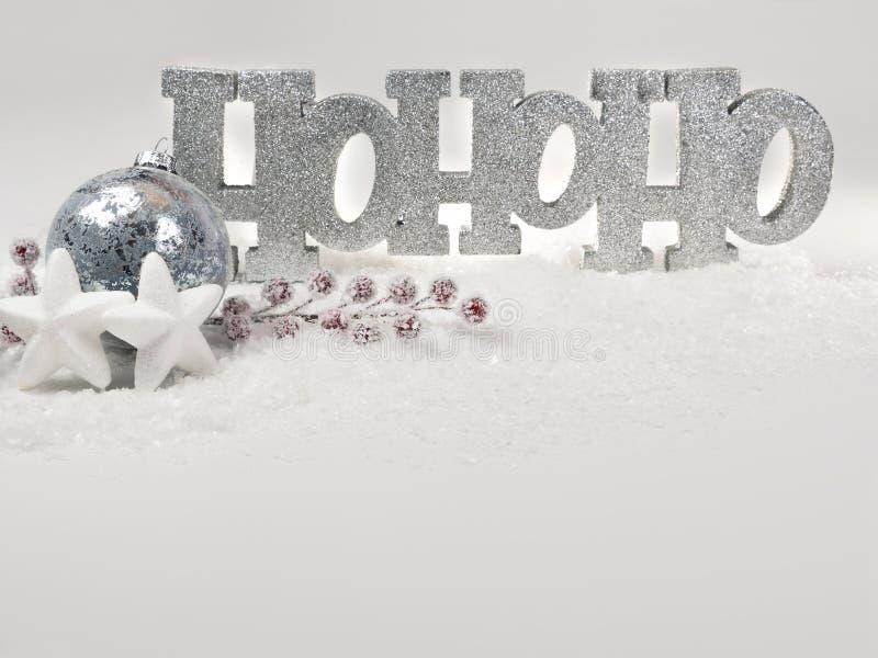 Cumprimentos das estações com mensagem brilhante de HoHoHo e a decoração festiva na neve imagens de stock royalty free
