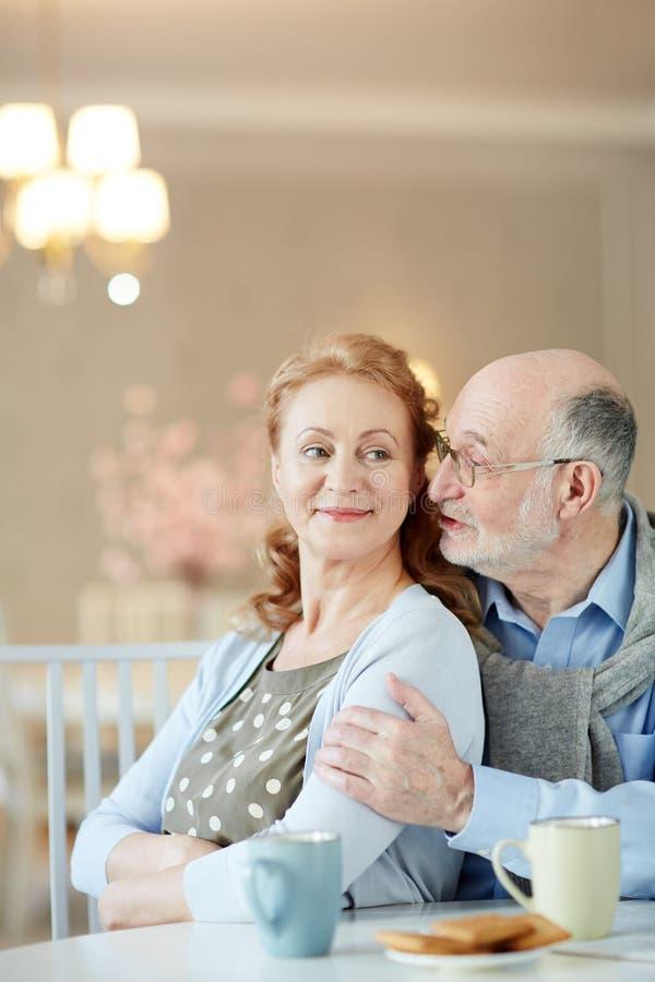 Cumprimentos de sussurro do homem idoso à esposa imagem de stock