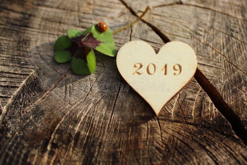 Cumprimentos do ano novo com um coração de madeira, um trevo afortunado e uma joaninha imagens de stock