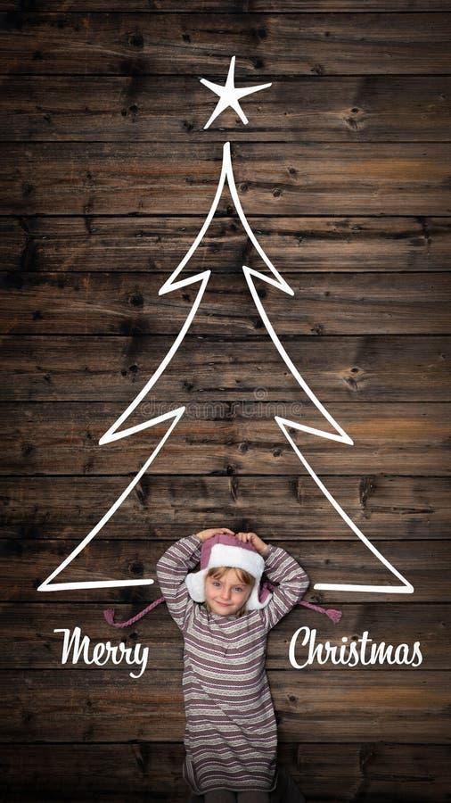 Cumprimentos do Feliz Natal na madeira escura vertical do vintage da vista superior Menina feliz da criança no pinho da árvore do foto de stock royalty free