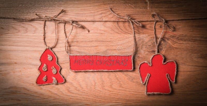Cumprimentos do Natal unidos a uma corda em um fundo de madeira imagem de stock
