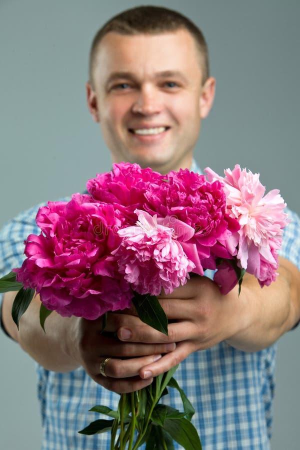 Cumprimentos Feche acima do homem de sorriso que dá o ramalhete das flores fotografia de stock