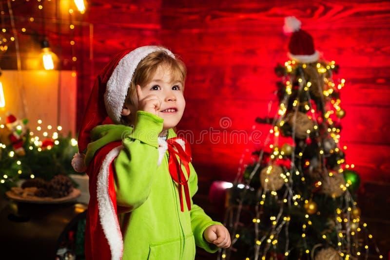 Cumprimentos para voc? sua fam?lia este Natal Feliz Natal e ano novo feliz Jogo bonito do menino perto da árvore de Natal imagem de stock