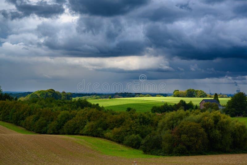 Dark cumulonimbus clouds with sun light spot over green autumn field. stock image